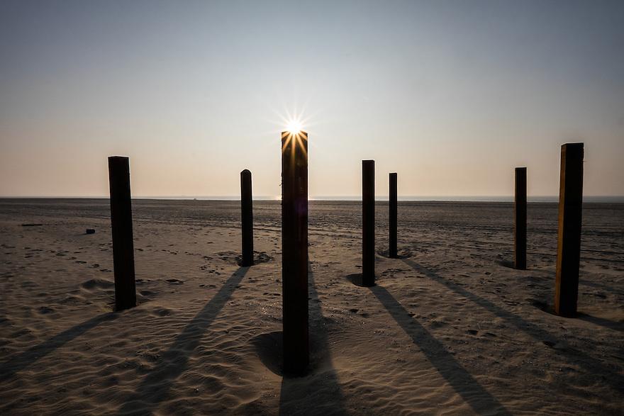 Nederland, Camperduin,  17 maart 2015<br /> Strand aan de voet van de hondsbosse zeewering bij Camperduin.  Ondergaande zon en palen in het zand.<br /> Foto: (c) Michiel Wijnbergh