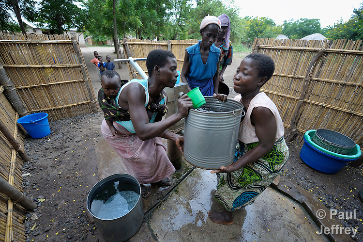 """Joyce Dzongololo (right) gets help from other women to lift a water container on her head, after filling it at the village pump in Chidyamanga, a village in southern Malawi that has been hard hit by drought in recent years, leading to chronic food insecurity, especially during the """"hunger season,"""" when farmers are waiting for the harvest."""