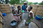 "Joyce Dzongololo (right) gets help from other women to lift a water container on her head, after filling it at the village pump in Chidyamanga, a village in southern Malawi that has been hard hit by drought in recent years, leading to chronic food insecurity, especially during the ""hunger season,"" when farmers are waiting for the harvest."