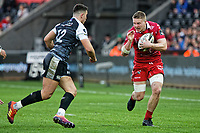 Ed Kennedy of the Scarlets (R) runs forward with the ball and tries to avoid Owen Watkin of the Ospreys (L) during the Guinness Pro14 Round 11 match between the Ospreys and the Scarlets at the Liberty Stadium, Swansea, Wales, UK. Saturday 22 December 2018