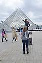 Paris, France. 09.05.2015. Tourist posing for a photo outside Le Louvre. Photograph © Jane Hobson.