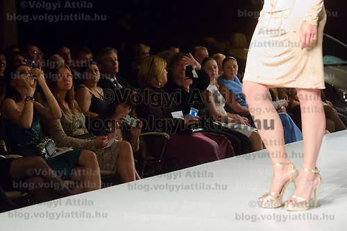 Viewers photograph a model with their mobile phones during a fashion show of the Maison Marquise collection by Hungarian fashion designer Bori Toth in Budapest, Hungary on May 28, 2013. ATTILA VOLGYI
