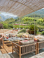Seating and tables by Damian Sanchez are arranged on an outside terrace shaded by a metal and natural cane pergola. The position of the terrace gives a view to the spectacular countryside beyond the garden.