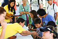 Visitors at the 40th Annual Ukulele Festival test out the ukuleles on display