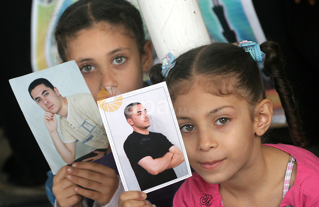Palestinian women and children hold pictures of jailed relatives during a protest calling for the release of Palestinian prisoners from Israeli jails at the Red Cross office in Gaza City on November 15,2010 .  Photo by Mohammed Asad