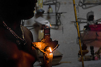 A Cuban man, the Palo religion follower, holds the Christian cross during the Palo initiation ritual in Santiago de Cuba, Cuba, August 1, 2009. The Palo religion (Las Reglas de Congo) belongs to the group of syncretic religions which developed in Cuba amongst the black slaves, originally brought from Congo during the colonial period. Palo, having its roots in spiritual concepts of the indigenous people in Africa, worships the spirits and natural powers but can often give them faces and names known from the Christian dogma. Although there have been strong religious restrictions during the decades of the Cuban Revolution, the majority of Cubans still consult their problems with practitioners of some Afro Cuban religion.
