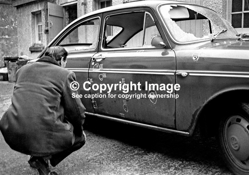 A detective at Dundonald RUC station, N Ireland, examines the vehicle in which Jack Mooney was killed and two colleagues, all Roman Catholics, were travelling when they arrived to start the night shift at the local Rolls-Royce factory. The UDA/UFF gun attack was on New Year's Day 1973, 1st January 1973. Jack Mooney, 31 years, was married with 2 children. His 62 year old father, Hugh Mooney, was among the passengers travelling in the vehicle. For more information see Lost Lives 728. 197301010002a<br />