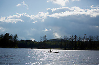A kayaker paddles in Tully Lake near Royalston, Massachusetts, USA.
