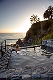 USA, California, Big Sur, Esalen, a woman sits in the Baths and looks out on the Big Sur coastline at sunset, the Esalen Institute