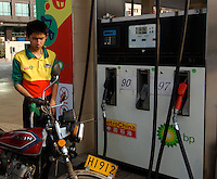 A petrol pump attendant at a Petrochina and BP (British Petroleum) gas station in Changping, China. BP is talking of a new merger with Sinopec, one of China's  oil producers..
