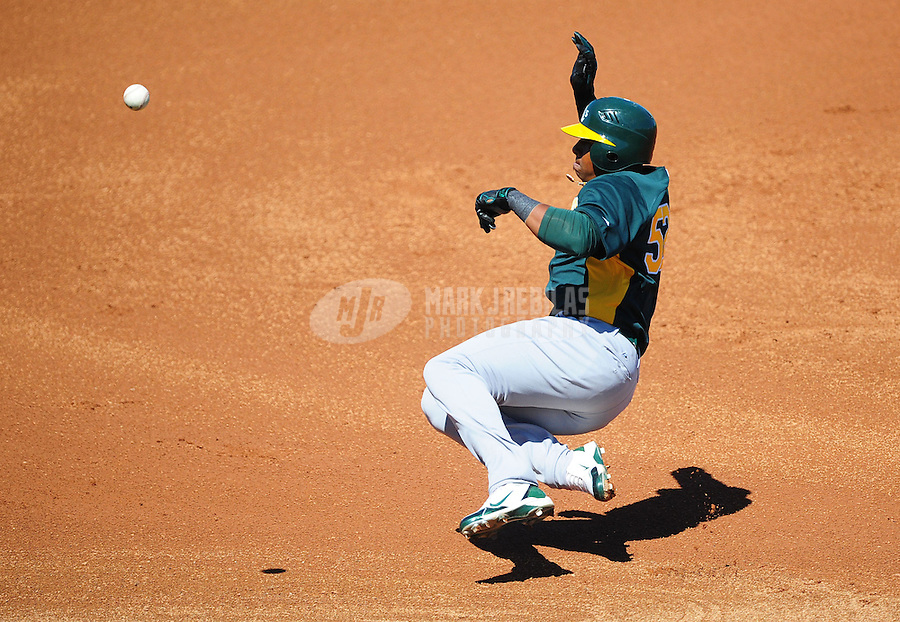 Mar. 15, 2012; Surprise, AZ, USA; Oakland Athletics base runner Yoenis Cespedes slides into third base in the first inning against the Texas Rangers at Surprise Stadium.  Mandatory Credit: Mark J. Rebilas-