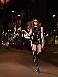 Beautiful young blond woman in a sexy outfit and siletto boots walking down a city street at night. Yonge Street, downtown Toronto, Ontario, Canada. Image © MaximImages, License at https://www.maximimages.com
