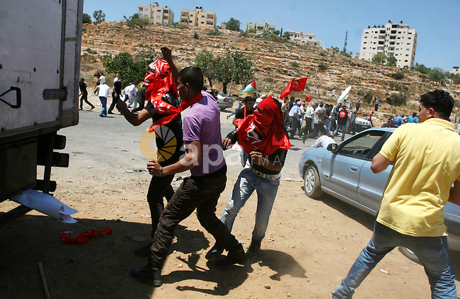 Palestinians hurl stones at Israeli troops, not seen, during a Democratic Front for the Liberation of Palestine (DFLP) demonstration supporting prisoners in Israeli jails outside the Ofer military prison, near the West Bank city of Ramallah, Thursday, Aug. 9, 2012. Palestinian witnesses said several protestors were injured during clashes with Israeli troops after the demonstration. Photo by Issam Rimawi
