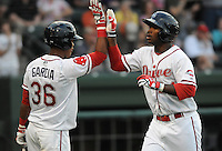 Left fielder Brandon Jacobs (24) of the Greenville Drive, Class A affiliate of the Boston Red Sox, is congratulated by Jose Garcia (36) after hitting a home run in a game against the Augusta GreenJackets on Opening Day, April 7, 2011, at Fluor Field at the West End in Greenville, S.C. Photo by Tom Priddy / Four Seam Images