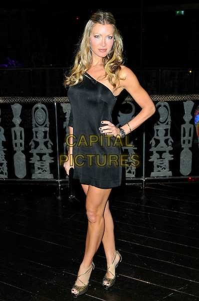 CAPRICE BOURRET.Liz McClarnon's 30th Birthday Party, Shaka Zulu Bar & restaurant, the Stables Market, Chalk Farm Road,.London, England, UK..April 13th 201.full length black dress one shoulder hand on hip.CAP/CAS.©Bob Cass/Capital Pictures.