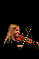 A young musician plays bluegrass music on the fiddle onstage during the 20th year of the Tosco Music Party, held at the Overcash Academic and Performing Arts Center Dale F. Halton Theater Central Piedmont Community College. The annual event, named after John Tosco, owner of the Tosco Music Studio, is designed to showcase professional and amateur musicians.