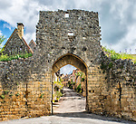An ancient stone gate leads into the village of Domme on the River Dordogne.