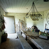 A rustic home-made chandelier hangs above a wooden refectory table in this workroom