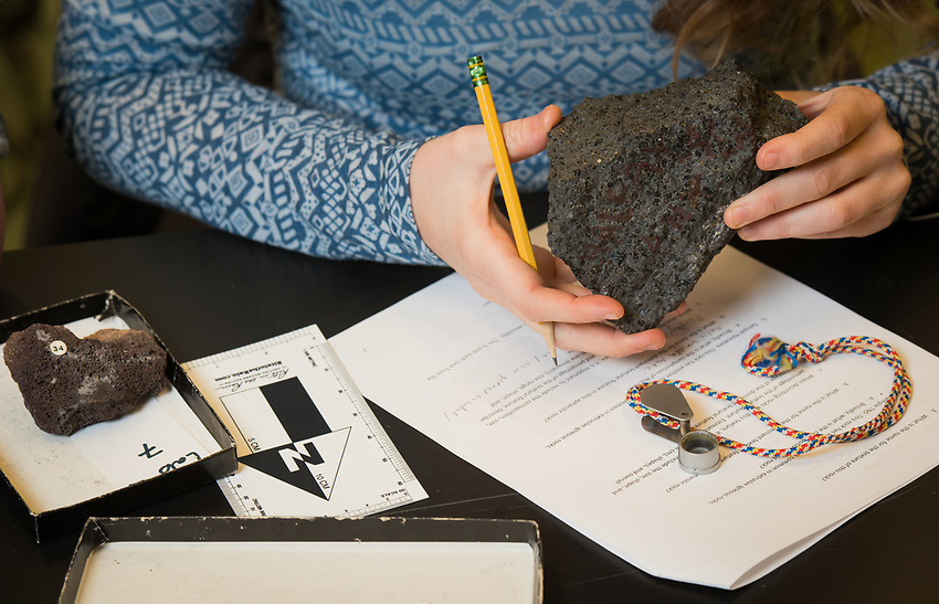 Monika Fleming interprets rock samples during a lab exercise for Geology Professor Erin Shea's Igneous and Metamorphic Petrology class (GEOL A322) in UAA's ConocoPhillips Integrated Science Building. Students in GEOL A322 learn to identify and classify igneous and metamorphic rocks; interpret different rock textures, structures, and mineralogy; and learn about the chemical and physical principles that control the formation of rocks.