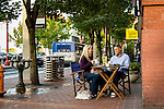 A couple enjoying coffee at a street cafe with a bus in the background.