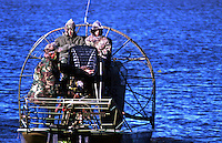 Hunters preparing airboat for hunting trip on a cold day in the Stick Marsh in Florida.