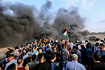 Palestinian protesters gather during clashes with Israeli troops in tents protest where Palestinians demand the right to return to their homeland at the Israel-Gaza border, in al-Bureij in the center of Gaza Strip on October 19, 2018. Photo by Mahmoud Khattab