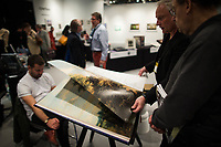 NEW YORK, NY - MARCH 30: People watch a book during the 37th edition of The Photography Show, presented by AIPAD on March 30, 2017 in Manhattan, New York. One of the world's most prestigious annual photography events, The Photography Show is the longest-running and foremost exhibition dedicated to the photographic medium, offering a wide range of museum-quality work, including contemporary, modern, and 19th-century photographs as well as photo-based art, video, and new media. Photo by VIEWpress/Eduardo MunozAlvarez