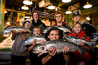 A family hold up salmon at Pike Place Market in Seattle Washington.