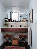 In a recessed area of the bathroom, a mirror is set over a washbasin set in a wood unit. Two folding stools sit beneath the unit.