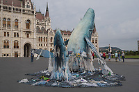 Whale sculptures swimming in plastic trash are put on display in front of the Hungarian Parliament to raise awareness for climate change and the ecologic consequences of disposable plastic bags and packaging and promoting the Plastic Free July movement to avoid these products for a month in downtown Budapest, Hungary on July 9, 2019. ATTILA VOLGYI