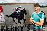 Jockey Bryan Cooper stands next to the mural of him, painted by Mike O'Donnell in St Brendan's NS Blennerville  on Monday.