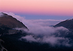 Low clouds fill Fall River Canyon beneath a colorful twilight sky, Rocky Mtn Nat'l Park, CO