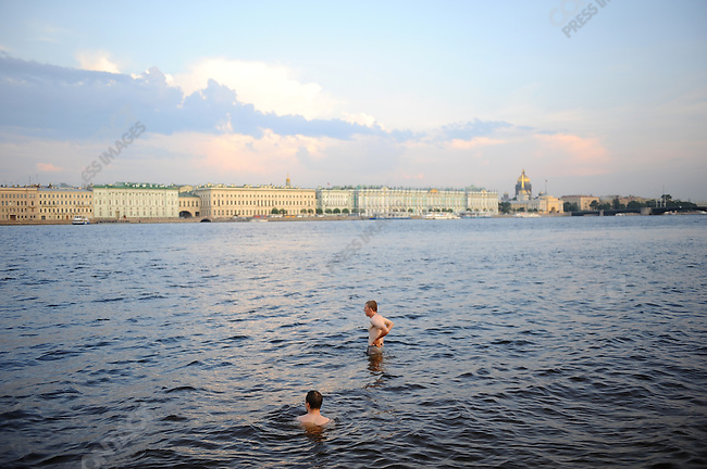 Two men bathed in the water's edge by the walls of the Peter and Paul Fortress as the light slowly dimmed in the late evening. White Nights, St. Petersburg, Russia, July 7, 2010
