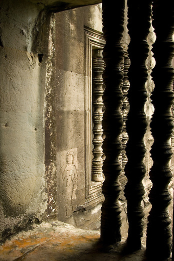 Lathe turned decorated windows at Angkor Wat. Since there would have been no electricity the windows allow light to pass through the temple. In the background you can see the beginnings of an apsara bas relief. Angkor Wat is home to almost 2000 apsaras or 'celestial nymphs'.