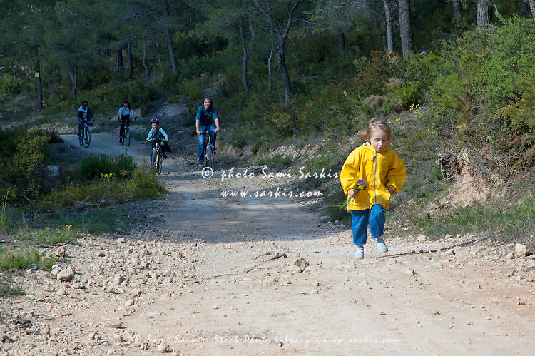 Girl running ahead of her family on a dirt road while they cycle behind, Vitrolles, Provence, France.