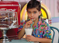 ITALIAN AMERICAN BOY (9) DRINKING MILK AT A SODA FOUNTAIN. ITALIAN-AMERICAN BOY (9). ORLANDO FLORIDA.