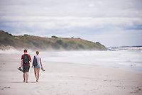 Tourists walking on Rarawa Beach, a popular and beautiful white sand beach in Northland Region, North Island, New Zealand
