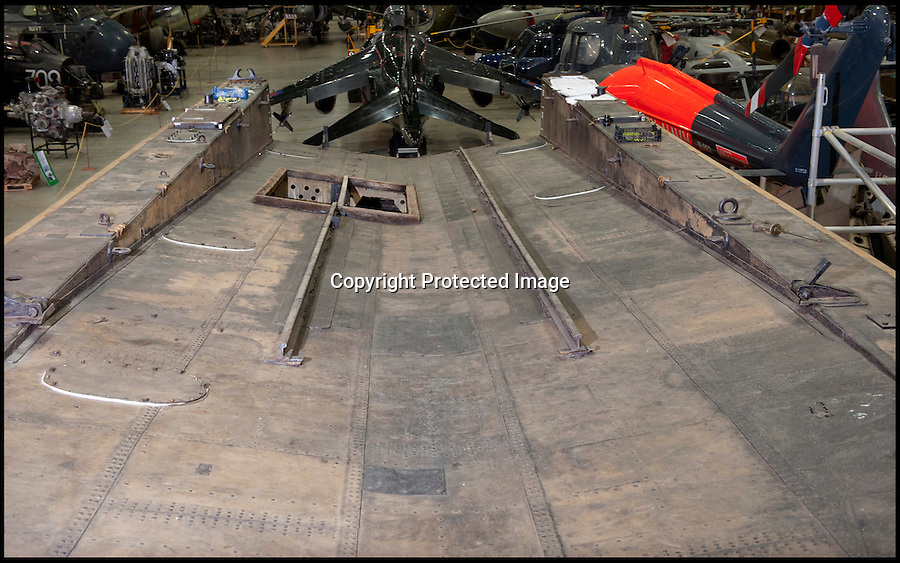 BNPS.co.uk (01202 558833)<br /> Pic: LauraJones/BNPS<br /> <br /> The wooden deck is yet to be added.<br /> <br /> Worlds first Aircraft Carrier restored.<br /> <br /> An amazing tale of bravery and ingenuity from the First World War has been revealed as the worlds first aircraft carrier has been restored at the Fleet air arm museum in Somerset.<br /> <br /> Measuring just 58ft long, the precarious craft was invented to counter the threat of Zepplin raids over London and enabled a plucky pilot to launch his Sopwith Camel at the enemy from the North sea before the feared airships could reach Britain.<br /> <br /> The tiny carriers were towed out from port behind a battleship with the aircraft strapped to the top of a wooden ramp. The crew and pilot would have to endure the conditions before an enemy was spotted and the ship then towed them into wind as fast as they could.<br /> <br /> The pilot had just 58ft of 'runway' to get the plane airborne or it would plummet into the sea with disastrous consequences.<br /> <br /> A team of seamen had to hold the plane back while the pilot got the engine up to speed then release the chocks at the right moment.<br /> <br /> Incredibly even if the plane made it into the air, the only way the pilot could land again was by crashing into the sea in the hope of being rescued.