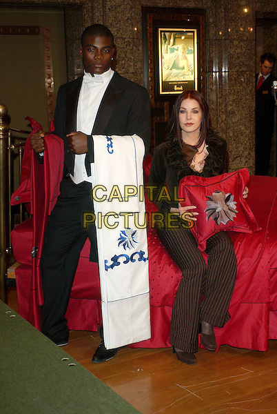 "PRISCILLA PRESLEY.Launches her bed linen range ""The Priscilla Presley Collection"" at the bed linen department, Harrods, London, UK. .April 5th, 2006 .Ref: BEL.full length brown ruffles shirt pinstripe sitting trousers.www.capitalpictures.com.sales@capitalpictures.com.© Capital Pictures."