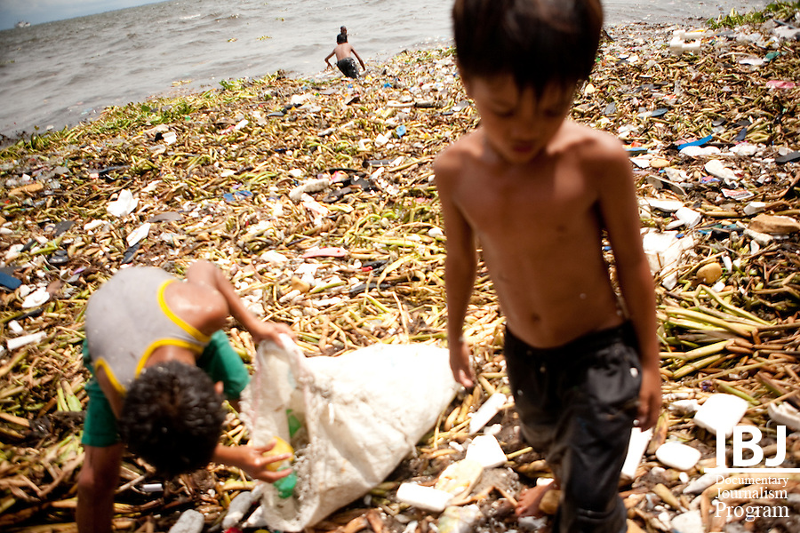 Near Manila's ports, children sort through trash to find recyclable material that can be turned in for money.