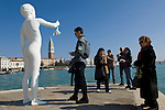 Venice-Italy - March 28, 2010 -- A security guard keeps an eye on the sculpture 'Boy with a Frog' (by the American artist Charles Ray) at Dorsoduro / Punta della Dogana Museum, ref. exhibition 'Mapping the Studio', the St. Marc's Campanile in the back -- art, culture, people -- Photo: © HorstWagner.eu
