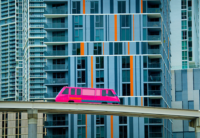 An elevated Metromover travels by high rise condominiums in the Brickell neighborhood of downtown Miami, Florida.  The free mass transit automated people mover has been a catalyst for downtown development.