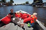 Nederland, Amsterdam, 29-05-2009 - Vader vaart in zijn vlet  in het Zijkanaal 1 richting  Het Ij met zijn twee kleine kinderen tijdens zijn papadag.  Met zijn laptop tussen zich in  houdt hij contact met zijn klanten.  Foto: Gerard Til