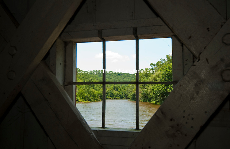 WEST CORNWALL, CT-071814JS08- The Housatonic River is seen through one of the viewing windows of the West Cornwall which will be celebrations its 150th anniversary. In honor of the event, artists are invited to a Paint the Bridge Day July 26. Melissa Andrews of the Economic Development Commission and Bianca Griggs of the Wish House are recreating an event that used to take place on the historic span. Painters, sculptors, photographers and all other artists are welcome to come with the goal of handing in their work by 2 p.m. at the Cornwall Bridge Pottery for exhibit and sale. A reception to be held the same day from 3 to 6 p.m. Seventy percent of each sale will go to the artist and 30 percent to the West Cornwall Village Improvement Association for maintenance of the parklike areas around the bridge. Also welcome is art created before that day. Each artist may submit one creation. The exhibit will be open for viewing July 27.<br /> Jim Shannon Republican-American