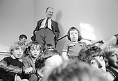 John Holt, American educationalist, listening to kids singing on the stairs during his visit to Julian's Primary School, Streatham, London.  1971.