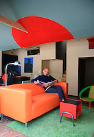 Bertrand Dessane pictured relaxing in the colourful living room of his tiny, loft apartment in Marseilles where the guest room and master bedroom are situated in compartments with hatches opening out to the living space and access is via a small central wooden staircase