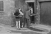 Bill Murphy, white jacket, in the doorway.  Moving equipment and books into the building, Scotland Road Free School, Liverpool  1971.  Also known as the Scotland Road or Scottie Road Free School it was founded and run by two teachers, John Ord and Bill Murphy (if I've got these names wrong, please tell me!) who worked with truanting kids and provided somewhere to go and things to do.  They begged and borrowed an old building, desks, books and an old ambulance for trips.