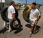 8/1994-Al Diaz/Miami Herald--In 1994 Cuban balseros turned the tiny fishing village of Cojimar into a major point of embarkation for thousands seeking a better life. Here, two men walk along the streets of Cojimar with their innertubes as they prepare to make their own rafts.