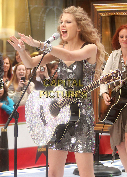 TAYLOR SWIFT .performs live on NBC's The TODAY Show, Rockefeller Center, New York, NY, USA, 26th October 2010..music concert gig on stage half length dress guitar silver grey gray patterned sleeveless hands  mouth open singing microphone bracelet sequined sequin.CAP/ADM/AC.©Alex Cole/AdMedia/Capital Pictures.