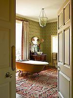 View through an open door to a bathroom with a claw foot bath and wallpaper by Robert Kime